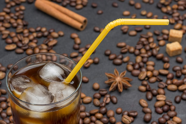 Szklanka mrożonej kawy, żółta słomka. na czarnym tle ziarna kawy, laska cynamonu, anyż.