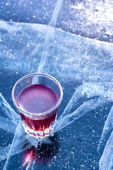 Szklanka nalewki stoi na lodzie jeziora bajkał. czerwony płyn w szklance świecącej w słońcu. widok z boku z góry. trochę śniegu na lodzie. pionowy.