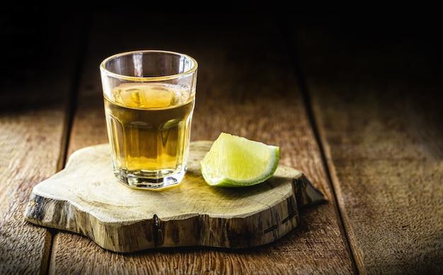 """Szklanka napoju alkoholowego z cytryną, destylowana z trzciny cukrowej, zwanego w brazylii """"pinga"""" lub """"cachaía"""", copyspace"""
