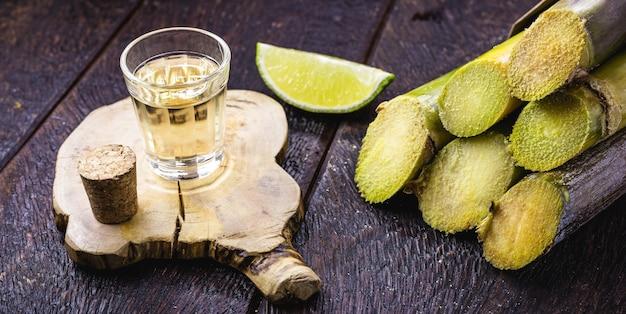 """Szklanka napoju alkoholowego z cytryną, destylowanego z trzciny cukrowej, zwanego w brazylii """"pinga"""" lub """"cachaía"""""""