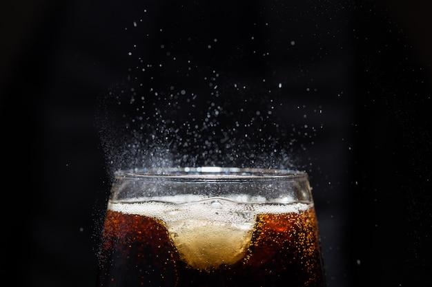 Szklanka napoju cola z solą. na czarnej ścianie.