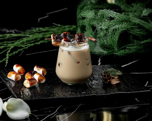 Szklanka napoju kawowego z lodem przyozdobionym prażonym piankiem