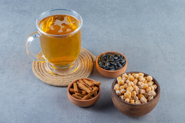 Szklanka napoju na podstawce obok miski z ciecierzycy, grzankami i nasionami, na marmurowej powierzchni.