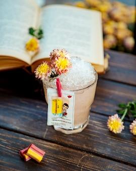 Szklanka napoju z lodem ozdobiona kwiatami i wkładką z miłości isgum