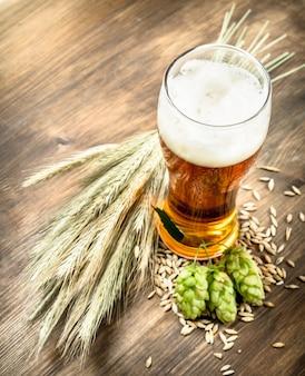 Szklanka naturalnego piwa na drewnianym stole.