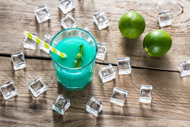 Szklanka niebieskiego curacao i soku koktajlowego