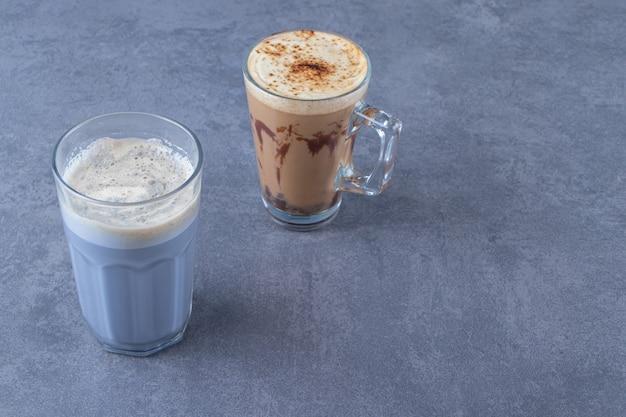 Szklanka niebieskiej kawy obok czekoladowego cappuccino, na niebieskim stole.