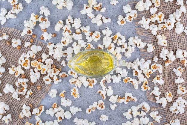 Szklanka oleju otoczona niechlujnie rozrzuconym stosem popcornu i ziaren na marmurowej powierzchni