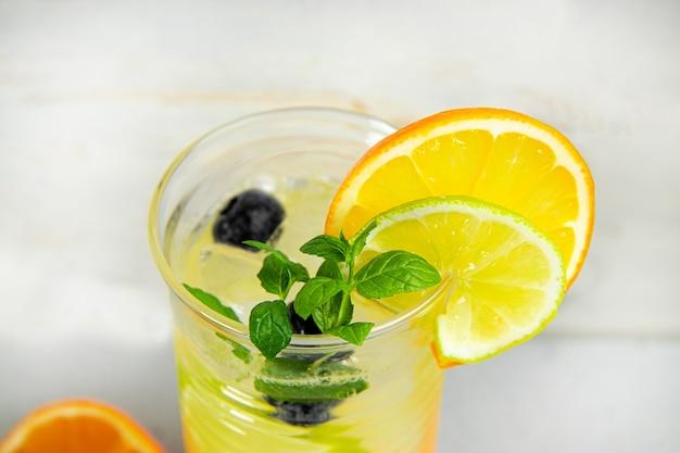 Szklanka orzeźwiającej letniej lemoniady z lodem. koktajl z jagodami i cytryną z bliska.
