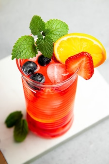 Szklanka orzeźwiającej letniej lemoniady z lodem. koktajl z truskawką i cytryną z bliska.