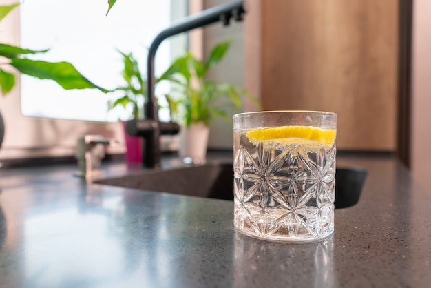 Szklanka orzeźwiającej wody z plasterkiem orzeźwiającej cytryny pod niskim kątem na blacie w kuchni z copyspace