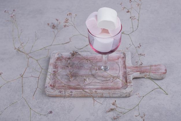 Szklanka pianek na desce z rośliną. wysokiej jakości zdjęcie