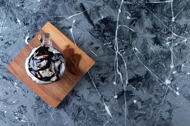 Szklanka pienistej zimnej kawy z bitą śmietaną i czekoladą na drewnianym talerzu.