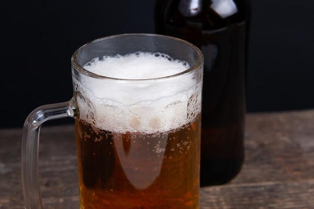 Szklanka piwa i butelki piwa na drewnianym stole
