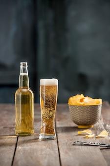 Szklanka piwa i chipsy ziemniaczane, pistacje na białym tle