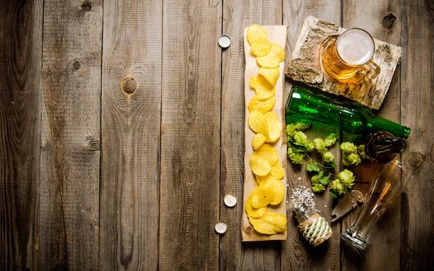 Szklanka piwa i frytki na drewnianym stole