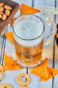 Szklanka piwa i frytki na niebieskim stole, z bliska.