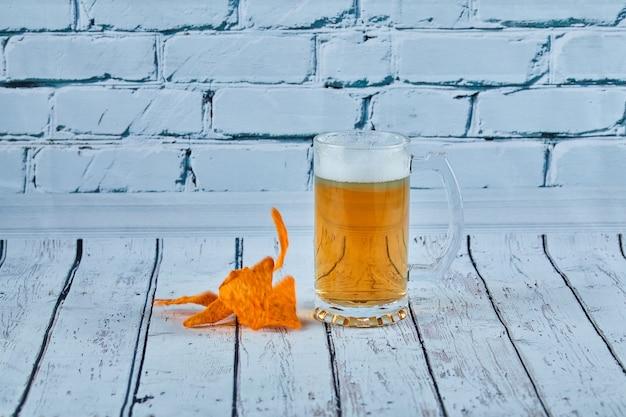 Szklanka piwa i frytki na niebieskim stole.