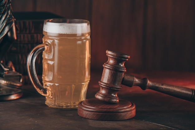 Szklanka piwa i młotek sędziowski jako symbol prawa na drewnianym stole