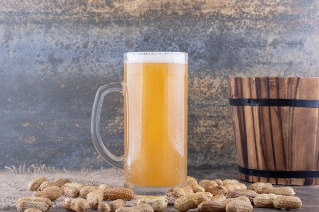 Szklanka piwa i porozrzucane orzeszki ziemne na marmurowym stole