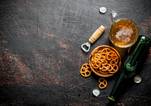 Szklanka piwa i precelki przekąski w misce. na ciemnym tle rustykalnym