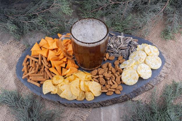 Szklanka piwa i przekąski na drewnianym kawałku. zdjęcie wysokiej jakości