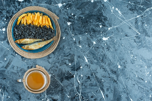 Szklanka piwa i przekąski na drewnianym talerzu na trójnogu, na niebieskim tle.
