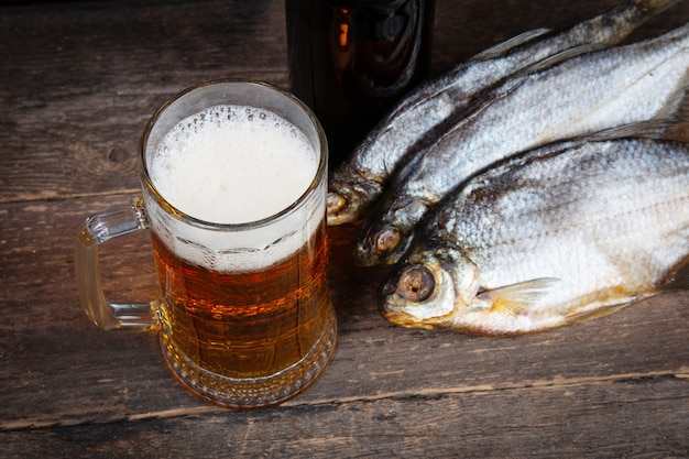 Szklanka piwa i suchej ryby na drewnianym stole