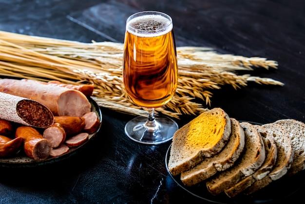 Szklanka piwa, kiełbasy i chleb na stole
