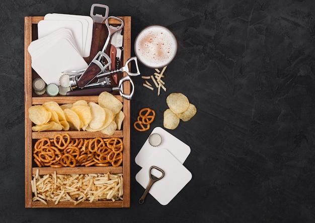 Szklanka piwa lager rzemieślniczego i otwieracz z pudełkiem przekąsek na tle czarnego stołu kuchennego. precel, chipsy i słone paluszki ziemniaczane w zabytkowym drewnianym pudełku z otwieraczami i podkładkami pod piwo. miejsce na tekst