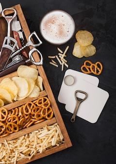 Szklanka piwa lager rzemieślniczego i otwieracz z pudełkiem przekąsek na tle czarnego stołu kuchennego. precel, chipsy i słone paluszki ziemniaczane w zabytkowym drewnianym pudełku z otwieraczami i podkładkami pod piwo.