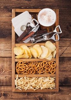Szklanka piwa lager w vintage pudełku otwieraczy do przekąsek i podkładek pod piwo na tle drewna. precel i chipsy oraz solony ziemniak.