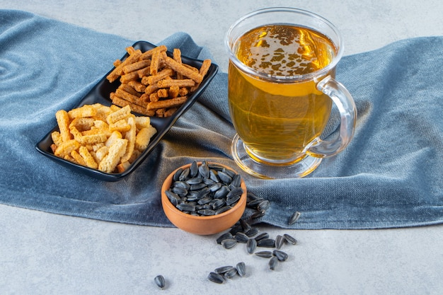 Szklanka piwa lager z miseczkami na przekąski na ręczniku, na marmurowej powierzchni.