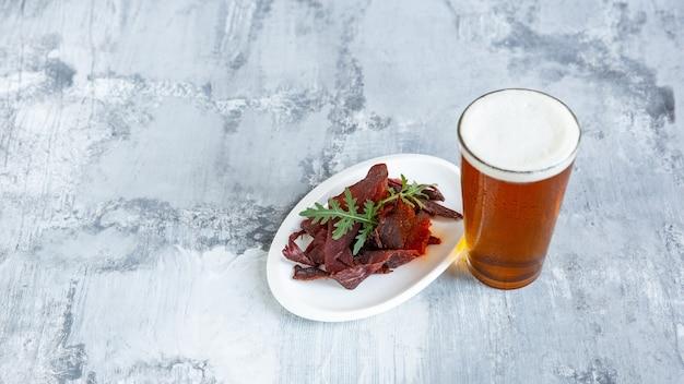 Szklanka piwa na białej kamiennej ścianie stołu.