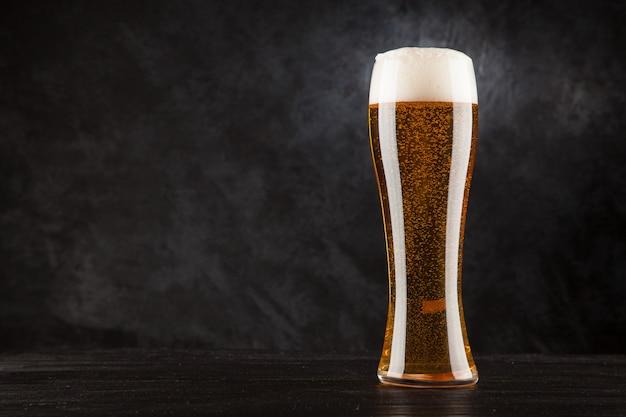 Szklanka piwa na ciemnym tle