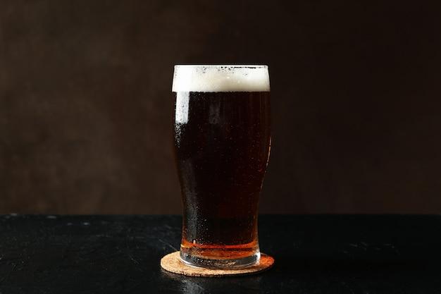 Szklanka piwa na czarnym stole na brązowym tle