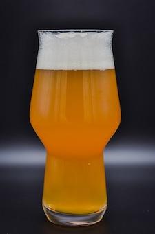 Szklanka piwa na czarnym tle wypełniona szklanym napojem na czarnym tle szklanka piwa