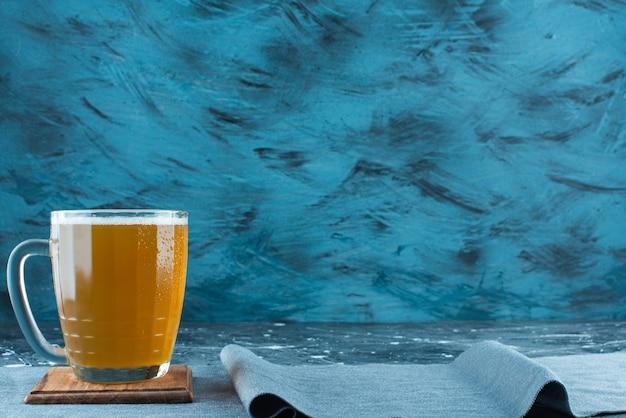 Szklanka piwa na desce na kawałkach materiału, na niebieskim stole.