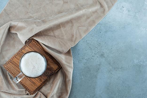 Szklanka piwa na desce na ręczniku, na niebieskim stole.