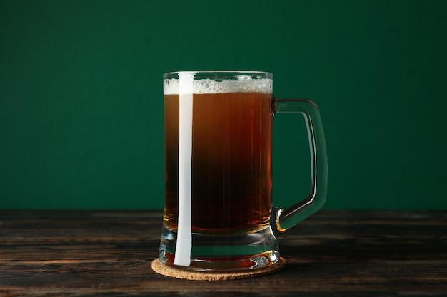 Szklanka piwa na drewnianym stole na zielonym tle