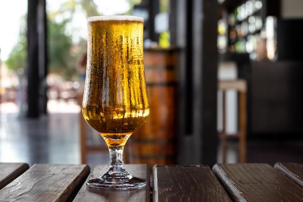 Szklanka piwa na drewnianym stole w pubie, barze. napój alkoholowy. strona, koncepcja wypoczynku.