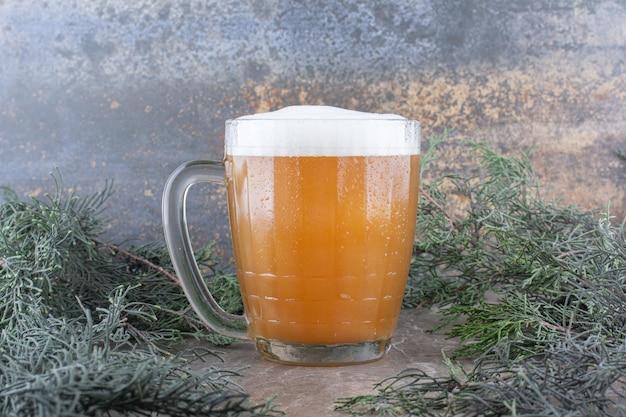 Szklanka piwa na marmurowym stole z gałęzi sosny. zdjęcie wysokiej jakości