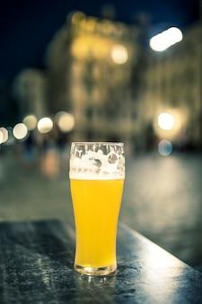 Szklanka piwa na stole w nocy