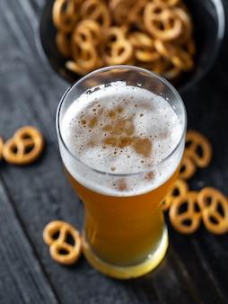 Szklanka piwa pszenicznego i tradycyjna przystawka z precla na stole