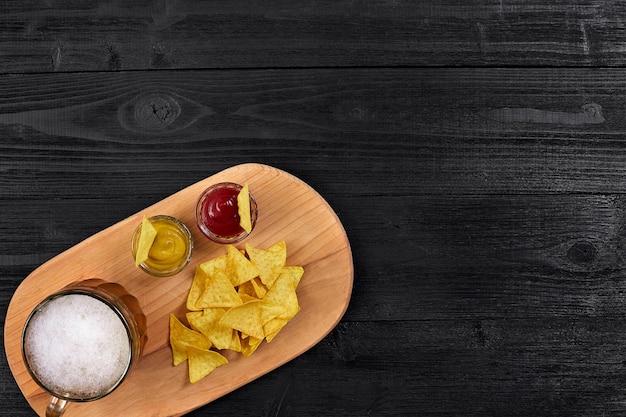 Szklanka piwa z chipsami nachos na drewnianym tle