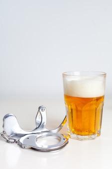 Szklanka piwa z kajdankami jako symbol nadużywania alkoholu