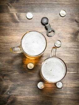 Szklanka piwa z korkami i otwieraczem do butelek. na drewnianym stole.