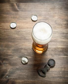 Szklanka piwa z korkami i otwieraczem do butelek na drewnianym stole.