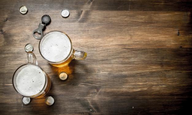 Szklanka piwa z korkami i otwieraczem do butelek