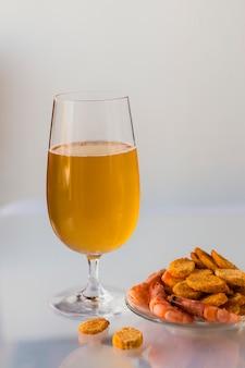 Szklanka piwa, z krewetkami i krakersami